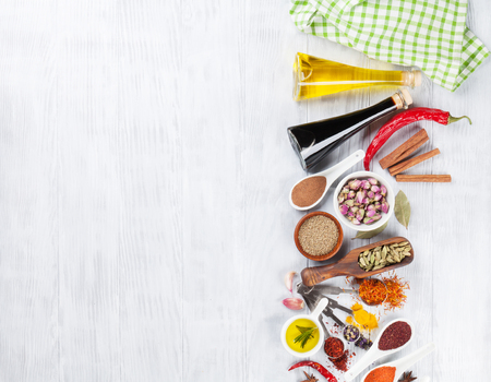 Herbs, condiments and spices on wooden background. Top view with copy space Banco de Imagens