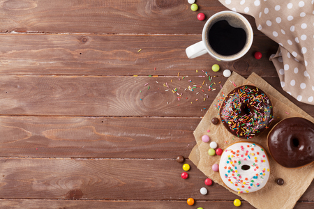 doughnut: Donuts and coffee on wooden table. Top view with copy space