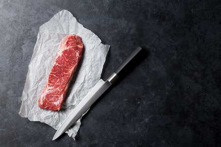 Raw striploin steak and kitchen knife over stone table. Top view with copy space