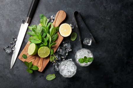 ingredient: Mojito cocktail making. Mint, lime, ice ingredients and bar utensils. Top view