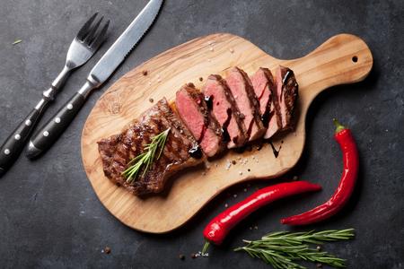 Gegrilltes Roastbeef Steak in Scheiben geschnitten an Bord über Steinschneidetisch. Aufsicht Standard-Bild - 56448210