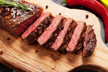 Gegrilde striploin gesneden biefstuk op snijplank over stenen tafel