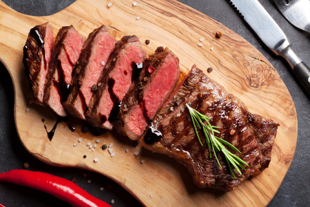 Grilled striploin sliced steak on cutting board over stone table. Top view