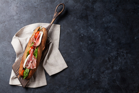 Ciabatta sandwich with romaine salad, prosciutto and mozzarella cheese on stone table. Top view with copy space Stockfoto