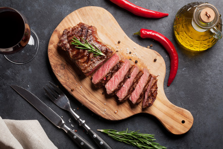 Grilled striploin sliced steak and red wine over stone table. Top view Stock Photo