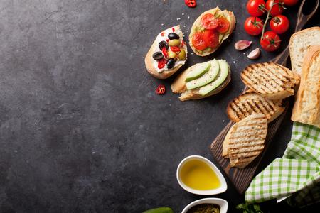 Toast-Sandwiches mit Avocado, Tomaten und Oliven auf Stein Hintergrund. Ansicht von oben mit Kopie Raum