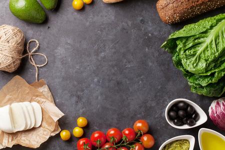 食材を調理します。石の背景にレタスのサラダ、アボカド、オリーブ、チーズ、パン、トマト チェリー。コピー スペース平面図