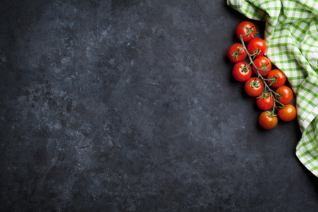 Ripe cherry tomatoes over stone kitchen table. Top view with copy space