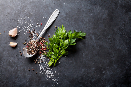 perejil: Ajo, pimienta y sal especias negras, blancas y rojas en la cuchara, hierba del perejil. Vista superior con espacio de copia