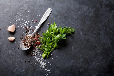 Knoflook, zwarte, witte en rode peper en zoutkruiden in lepel, peterselie kruiden. Bovenaanzicht met kopie ruimte