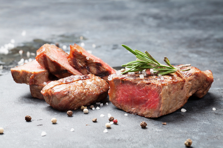 Grilled striploin sliced steak on stone table 스톡 콘텐츠