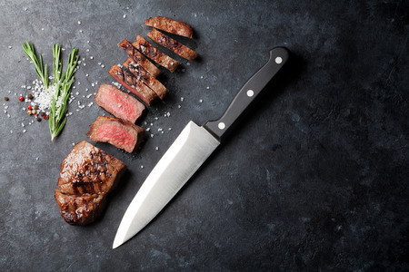 Grilled sliced beef steak on stone table. Top view with copy space Standard-Bild