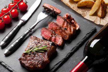 carne asada: filete de lomo en rodajas a la plancha con patatas y vino tinto sobre la mesa de piedra