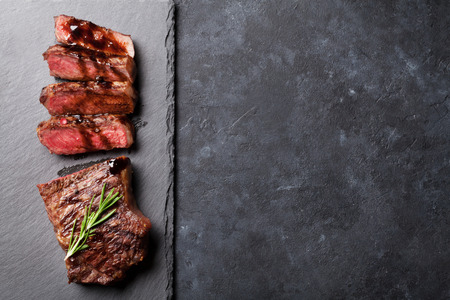 bbq background: Grilled sliced beef steak with balsamico and rosemary on stone table. Top view with copy space