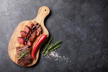 돌 테이블 위에 커팅 보드에 구운 슬라이스 쇠고기 스테이크. 복사 공간 상위 뷰 스톡 콘텐츠