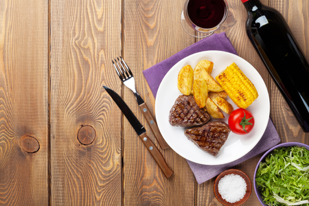 grilled potato: Steak with grilled potato, corn, salad and red wine on wooden table. Top view with copy space
