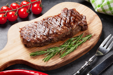 Grilled beef steak on cutting board over stone table Stock Photo