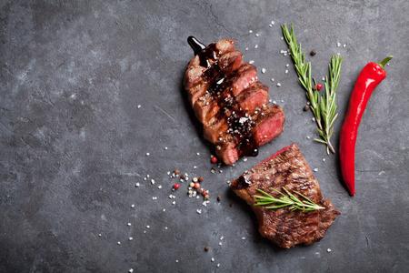 Gegrilltes geschnittenes Rindfleisch Steak mit Balsamico und Rosmarin auf Steintisch. Standard-Bild - 57560552