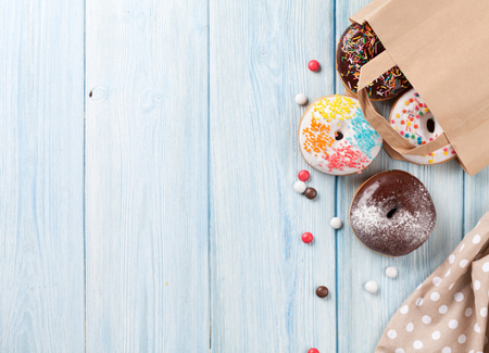 paper bag: Colorful donuts in paper bag on wooden table. Top view with copy space