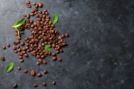 Coffee beans and mint leaves on dark stone table. Top view with copy space