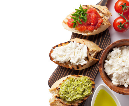 ensalada de frutas: Toast sandwiches with tomatoes, pesto and cheese. Isolated on white background