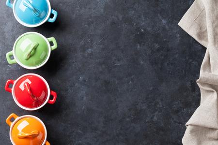 utensilios de cocina: cacerolas de colores sobre fondo mesa de piedra. Vista superior con espacio de copia Foto de archivo