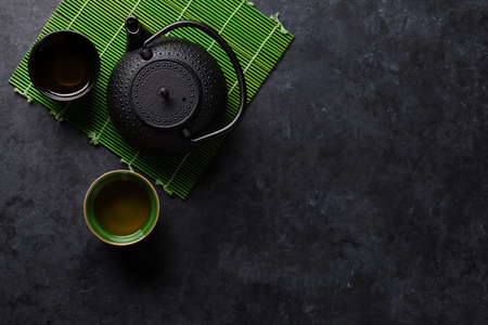 Green tea cups and teapot on stone table. Top view with copy space