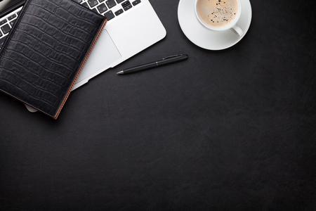 Kancelářský kožený stolní pracovní stůl s laptopem, šálkem kávy, poznámkový blok a pero. Pohled shora s kopírovacím prostorem