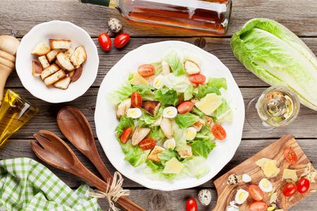 pollo a la brasa: saludable ensalada fresca y el vino blanco de mesa de madera. Vista superior