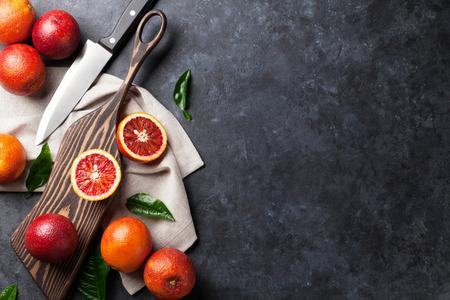 jugo de frutas: Frutas frescas de naranja rojo en la mesa de piedra. Vista superior con espacio de copia