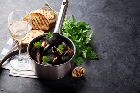 Muscheln im kupfernen Topf und im Weißwein auf Steintabelle. Zeigen Sie mit Kopienraum an Standard-Bild - 57890991