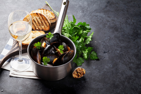 Mussels in copper pot and white wine on stone table. View with copy space