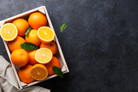 Fresh orange fruits in wooden box on stone table. Top view with copy space