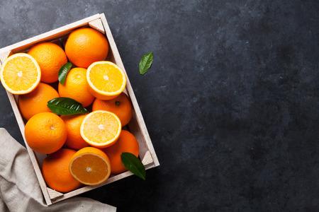 Frische orange Früchte in Holzkiste auf Steintisch. Ansicht von oben mit Kopie Raum
