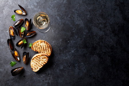 Mussels, bread toasts and white wine on stone table. View with copy space
