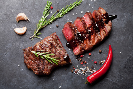 dark meat: Grilled sliced beef steak with balsamico and rosemary on stone table. Top view