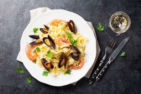 Pasta con pesce e vino bianco sul tavolo di pietra. Cozze e gamberi. Vista dall'alto Archivio Fotografico - 57836262