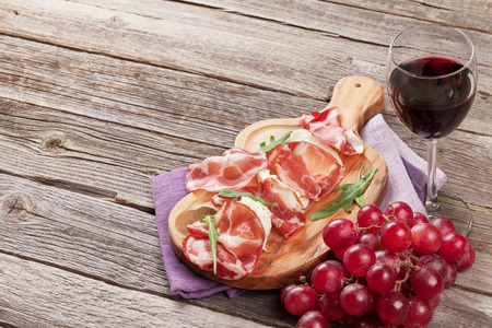 glass of white wine: Prosciutto and mozzarella with red wine on wooden table Stock Photo