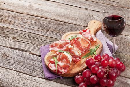 Prosciutto y mozzarella con vino tinto en mesa de madera