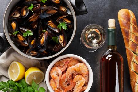 pan y vino: Mejillones, camarones y vino blanco en mesa de piedra. Vista superior