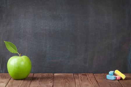 las manzanas y las tizas en la mesa de sala de clase delante de la pizarra. Ver con espacio de copia