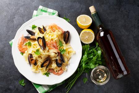 石のテーブルの上に白ワインと魚介類のパスタ。ムール貝とエビ。トップ ビュー