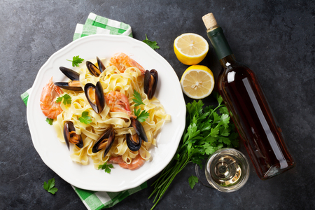 Pasta con pesce e vino bianco sul tavolo di pietra. Cozze e gamberi. Vista dall'alto