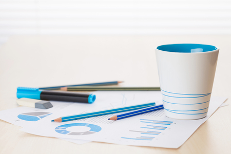 wood blinds: Office workplace with coffee cup, supplies and reports on wood desk table in front of window with blinds