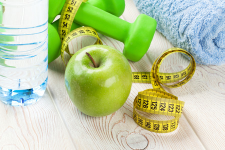dumbell: Healthy food and fitness. Apple, dumbells, water bottle and tape measure