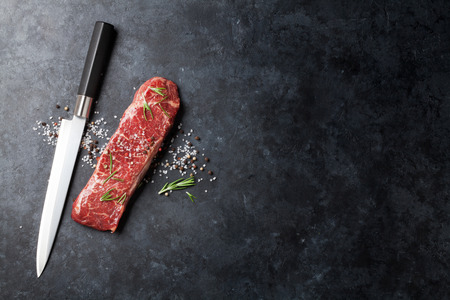生サーロイン ステーキ ローズマリー、塩、コショウの石のテーブル上の料理します。コピー スペース平面図 写真素材