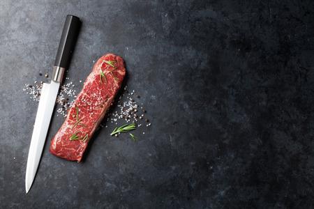 cuchillo: Lomo de filete sin procesar con romero, sal y pimienta cocinar sobre mesa de piedra. Vista superior con espacio de copia
