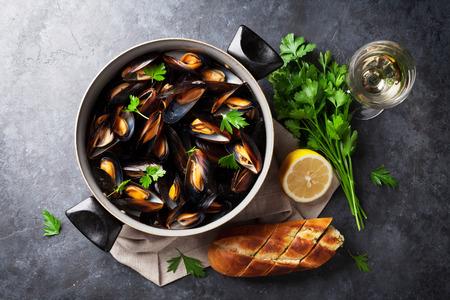 ムール貝の銅鍋と石のテーブルの上に白ワイン。トップ ビュー