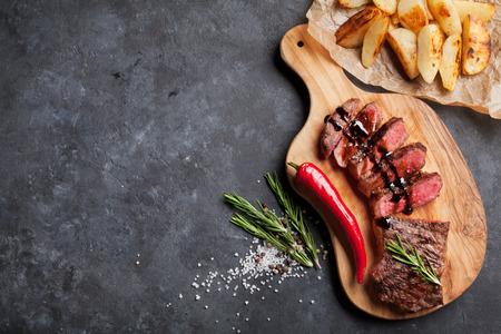 Grillé tranché steak de boeuf sur une planche à découper sur table en pierre. Vue de dessus avec copie espace