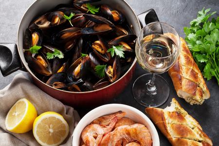 pan y vino: Mejillones, camarones y vino blanco en mesa de piedra Foto de archivo